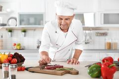 Professional chef cooking meat on table Royalty Free Stock Photography