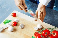 Professional chef cuts vegetables with a sharp knife from Damasc. Us steel. Mixed media Royalty Free Stock Images