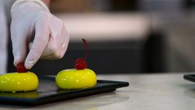 Professional chef decorating colorful desserts. Kitchen art. Sliding shot of a row of colorful glazed desserts being decorated by a professional chef at his stock footage