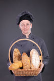 Professional chef in a gray suit holding a basket of bread Royalty Free Stock Image