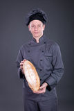 Professional chef in a gray suit holding bread in his hand Royalty Free Stock Images