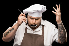 Professional chef in hat and apron tasting dish from ladle Royalty Free Stock Image