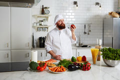 Professional chef holding fresh tomato Royalty Free Stock Photos