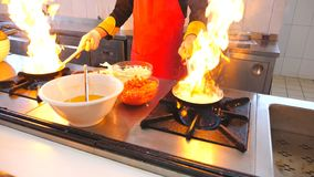 Professional chef holding two pans and cooking flambe style dish in modern kitchen of restaurant. Male cook frying