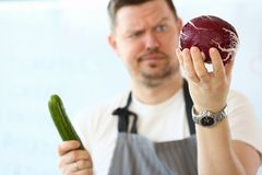 Professional Chef Holding Whole Purple Cabbage. Frustrated Man with Green Cucumber in Hand. Organic and Fresh Cuke for Vegan. Healthy Raw Food. Dieting Concept royalty free stock photography