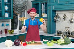 Professional Chef on kitchen cooking vegetables. Cook in red apron and cap. Man holds knife and paprika in hands on kitchen. Stock Image