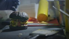 Professional chef makes a burger from ready-made ingredients. Finishes the burger and is ready to serve the client. Professional chef makes a burger from ready stock video footage