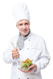 Professional chef mixing vegetable salad in a bowl on a white stock photo