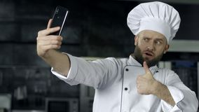 Professional chef posing at kitchen. Chef making selfie photo with mobile phone. Professional chef posing at kitchen. Male chef making selfie photo with mobile stock video