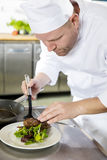 Professional chef prepare meat dish at restaurant Stock Image