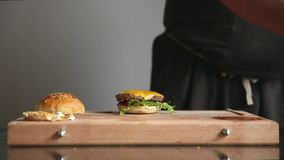 A professional chef prepares a cheeseburger with a big chop and a salad. Time laps. A professional chef prepares a cheeseburger with a big chop and a salad stock video