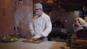 Professional chef prepares a delicious dish of slicing vegetables on a wooden kitchen board. Gourmet cooking concept. Professional chef prepares a delicious stock video