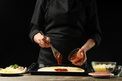 Professional chef prepares Italian pizza, spreads tomato sauce. On a black background, horizontal photo. Concept of cooking stock photo