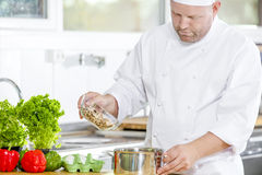 Professional chef preparing food in large kitchen Royalty Free Stock Photos