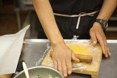 Professional chef rolling out dough Royalty Free Stock Image