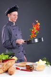 Professional chef throws food in the pan Royalty Free Stock Image