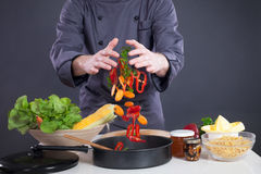 Professional chef throws food in the pan Royalty Free Stock Images