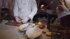 A professional chef in a white jacket and rubber chef gloves prepares a delicious dish of fish and fresh vegetables. The. Professional chef in a white jacket and stock footage