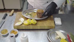 Professional chefs hands in black latex gloves rubs a piece of veal in the metal plate, marinating meat. Kitchen table. Chefs hands in black latex gloves rubs a stock footage