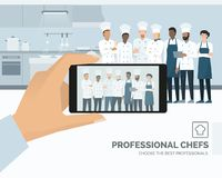 Professional chefs posing in the restaurant kitchen. A man is taking a picture using a smartphone, subjective point of view Royalty Free Stock Photography