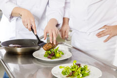 Professional chefs prepares steak dishes at restaurant. Chef and his assistant prepare meat dish with fresh salad in a professional kitchen at restaurant or Royalty Free Stock Images
