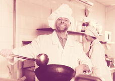 Professional chefs working at take-away. Cheerful professional chefs working in restaurant kitchen stock photo