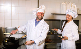 Professional chefs working at take-away. Positive professional chef and cook working at take-away restaurant kitchen royalty free stock images