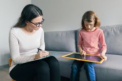 Professional child psychologist talking with child girl in office, child draws a drawing royalty free stock photography