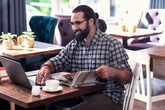 Professional Chinese tutor preparing for the class sitting in cafeteria. Chinese tutor. Professional smart bearded Chinese tutor preparing for the class sitting stock photo