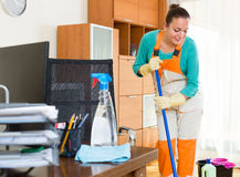 Professional cleaner  cleaning the office. Happy professional young european cleaner  cleaning the office Royalty Free Stock Photo
