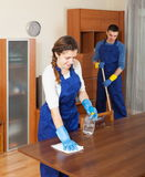 Professional cleaners cleaning furniture. And floor in room Stock Photography