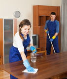 Professional cleaners dusting wooden furiture. At living room stock photo