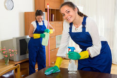 Professional cleaners make cleaning. Positive professional cleaners in uniform cleaning at the living room stock images