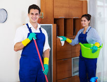 Professional cleaners in overalls with supplies. Young cleaners whiping surfaces and dusting in office royalty free stock images