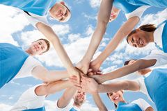 Professional cleaners piling hands against sky Royalty Free Stock Images