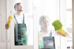 Professional cleaners cleaning windows. Professional cleaners with yellow gloves cleaning windows at a home royalty free stock photos