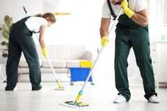 Professional cleaning crew washing floor. Professional cleaning crew washing the floor in a flat stock photography