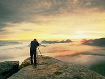 Professional on cliff. Nature photographer takes photos with mirror camera on peak of rock. Dreamy fog. Professional on cliff. Nature photographer takes photos Stock Photo