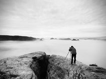 Professional on cliff. Nature photographer takes photos with mirror camera on peak of rock. Dreamy fog. Professional on cliff. Nature photographer takes photos Royalty Free Stock Photography