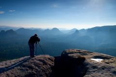 Professional on cliff. Nature photographer takes photos with mirror camera on peak of rock. Dreamy blue fogy landscape, Royalty Free Stock Image