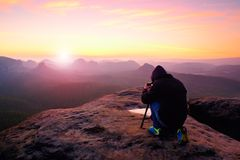 Professional on cliff. Nature photographer takes photos with mirror camera on peak of rock. Stock Photos