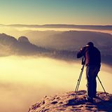 Professional on cliff. Nature photographer takes photos with mirror camera on rock. Dreamy fogy landscape, spring orange pink mist Stock Photo