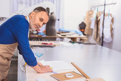 Professional cobbler drawing a shoe. This is a good idea, tailor drawing on a paper and smiling royalty free stock photos