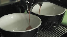 Professional coffee machine makes coffee in two black and white mugs in a cafe. pouring hot coffee drink into the cup. white steam stock footage