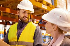 Joyful positive man looking at his female colleague royalty free stock photo