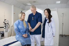 Professional With Colleague And Patient Using Computer Before MR Stock Images