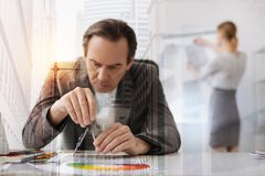 Professional concentrated male engineer using compasses. Stick to accuracy. Waist up of a serious senior engineer sitting at the table and using compasses while Royalty Free Stock Photos