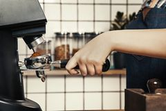 Professional barista grinds coffee at a scandinavian-style coffee shop. stock photos