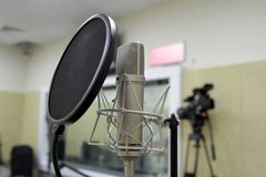 Professional condenser studio microphone over the musician blurred background and audio mixer, Musical instrument Concept. Professional condenser studio Stock Photos