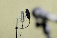 Professional condenser studio microphone over the musician blurred background and audio mixer, Musical instrument Concept. Professional condenser studio Royalty Free Stock Images